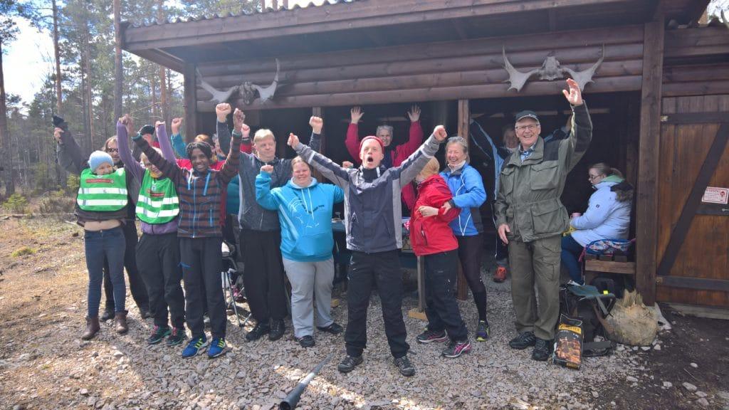 Bilde av Aktiv Fritid gjengen ute på tur som heier og smiler til kamera med hendene i været.